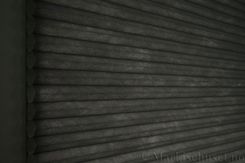 Duette tekstil serien Duotone 32mm 294034-7131 Koksgrå farge. Bildet er tatt med lys bakfra.