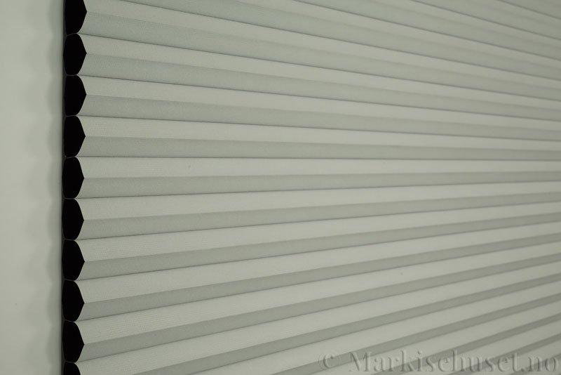 Duette gardin Blackout 32mm 294041-0633 Delfingrå farge. Bildet er tatt med lys forfra. Serien Duette® Fixé 32 Blackout er lystett.
