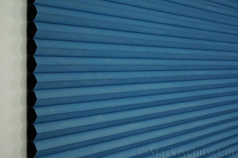 Duette gardin Blackout 32mm 294041-2534 Himmelblå farge. Bildet er tatt med lys forfra. Serien Duette® Fixé 32 Blackout er lystett.
