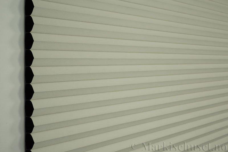 Duette gardin Blackout 32mm 294041-4434 Benhvit farge. Bildet er tatt med lys forfra. Serien Duette® Fixé 32 Blackout er lystett.