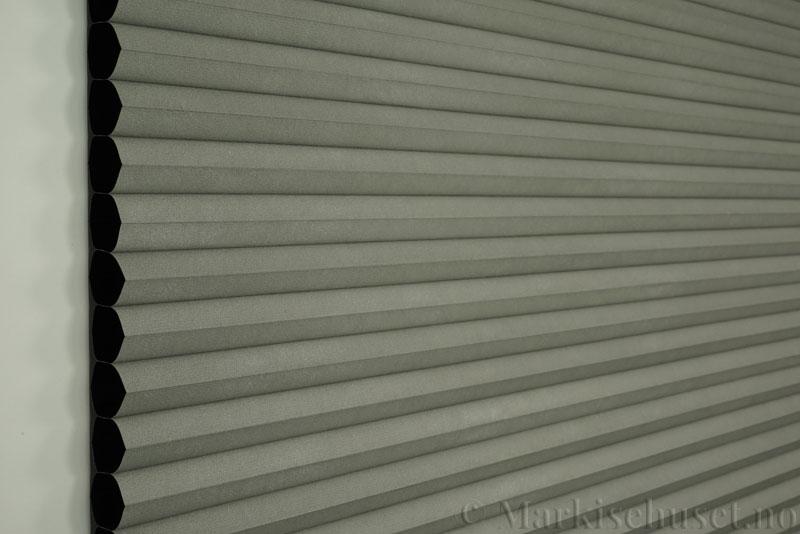 Duette gardin Blackout 32mm 294041-7033 Musegrå farge. Bildet er tatt med lys forfra. Serien Duette® Fixé 32 Blackout er lystett.