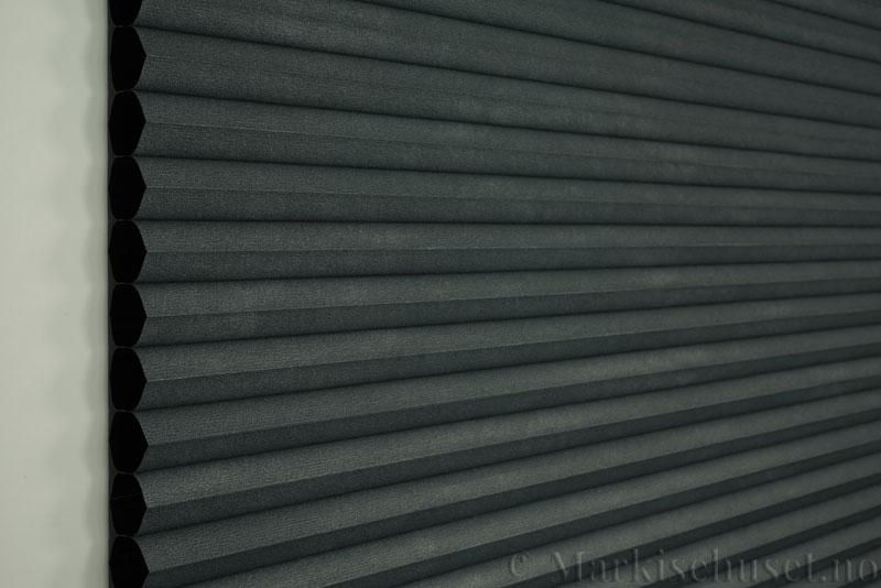 Duette gardin Blackout 32mm 294041-7132 Antrasit farge. Bildet er tatt med lys forfra. Serien Duette® Fixé 32 Blackout er lystett.