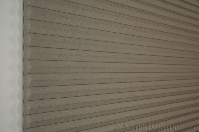 Duette gardin Batiste 32mm 294050-4532 Kaffegrå farge. Bildet er tatt med lys forfra.