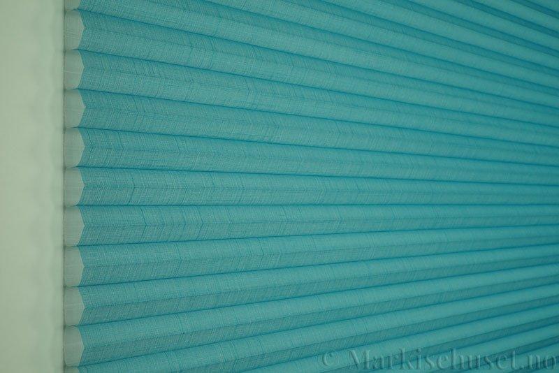 Duette gardin Batiste Sheer 32mm 294053-3932 Turkisblå farge. Bildet er tatt med lys forfra.