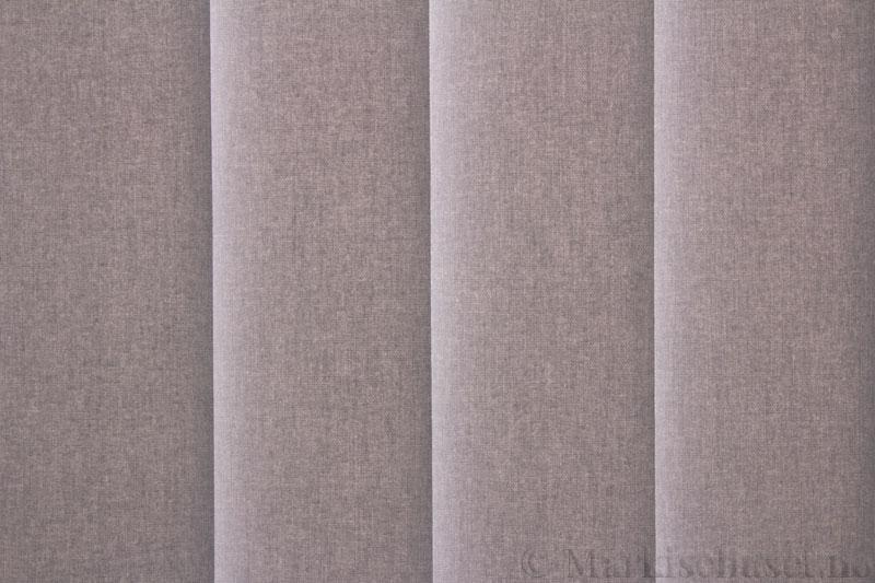 Lamellgardin tekstil serien Lumina 251625-0719 farge Lys Grå. Bildet er tatt med lys bakfra.