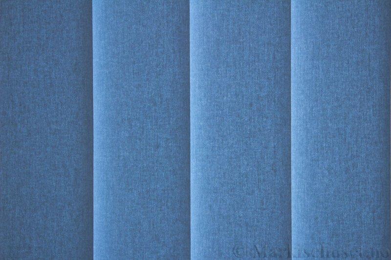 Lamellgardin tekstil serien Lumina 251625-2652 farge Lys Gråblå. Bildet er tatt med lys bakfra.