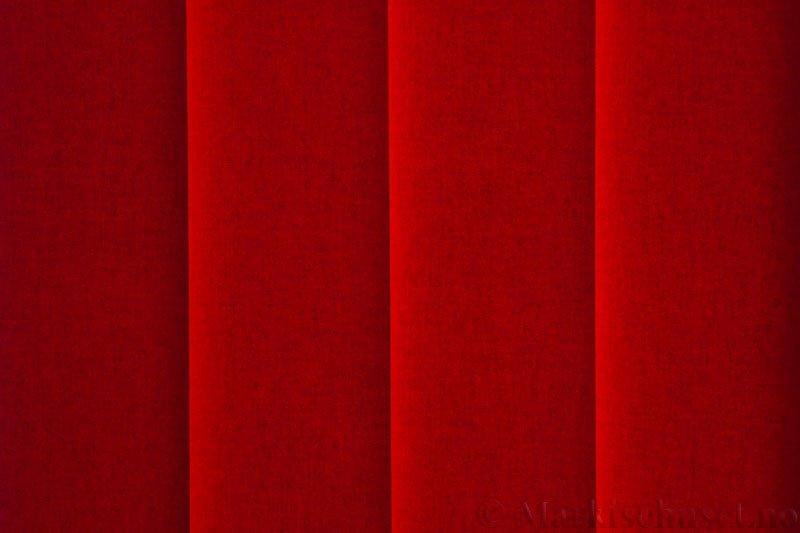 Lamellgardin tekstil serien Lumina 251625-5730 farge Tangorød. Bildet er tatt med lys bakfra.