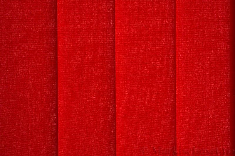 Lamellgardin tekstil serien Paris 2400 farge Tangorød. Bildet er tatt med lys bakfra.