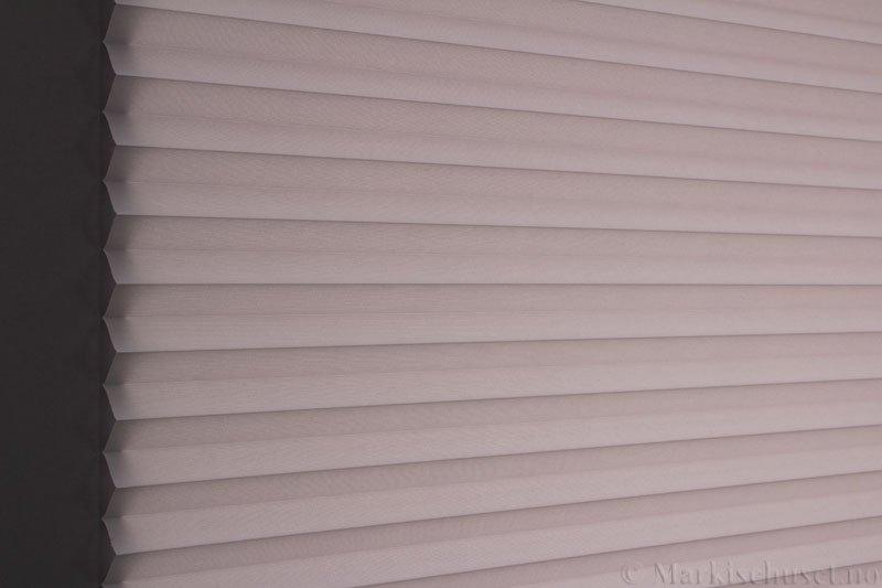 Plisségardin tekstil Baseline Dustblock 290467-0952 Lysegrå farge. Bildet er tatt med lys bakfra.