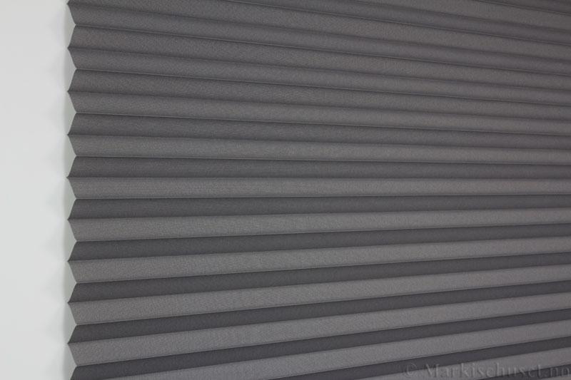 Plisségardin tekstil Baseline Dustblock 290467-1510 mellomgrå farge. Bildet er tatt med lys forfra.