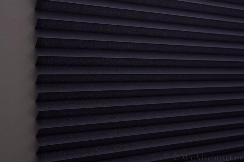 Plisségardin tekstil Baseline Dustblock 290467-2500 Marineblå farge. Bildet er tatt med lys bakfra.