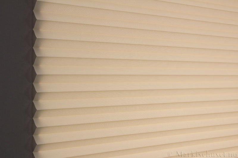Plisségardin tekstil Baseline Dustblock 290467-4420 Lys Beige farge. Bildet er tatt med lys bakfra.