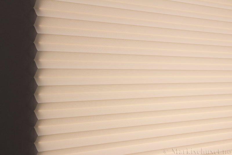 Plisségardin tekstil Baseline Dustblock 290467-4800 Lys Beige farge. Bildet er tatt med lys bakfra.