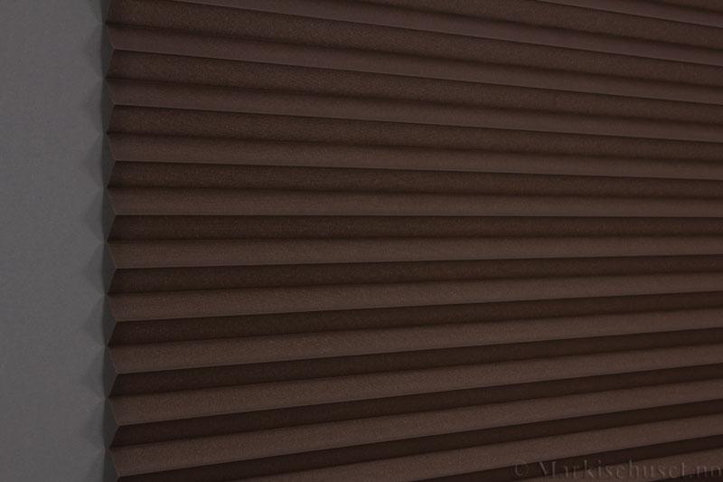 Plisségardin tekstil Baseline Dustblock 290467-4888 Brun farge. Bildet er tatt med lys bakfra.