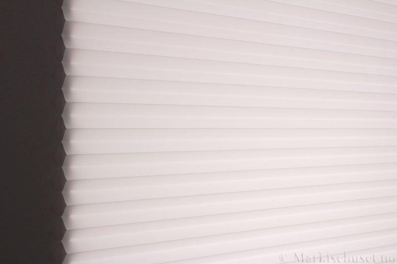 Plisségardin tekstil Uno Dustblock 290520-0204 Eggehvit farge. Bildet er tatt med lys bakfra.