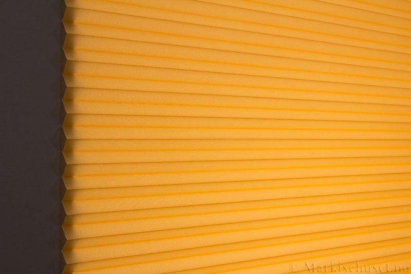 Plisségardin tekstil Uno Dustblock 290520-4200 Gul farge. Bildet er tatt med lys bakfra.