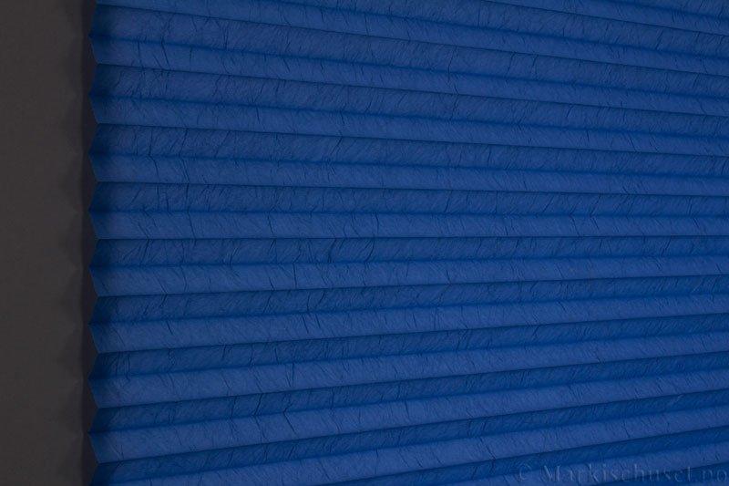Plisségardin tekstil Crush Dustblock 290521-2603 Marinblå farge. Bildet er tatt med lys bakfra.