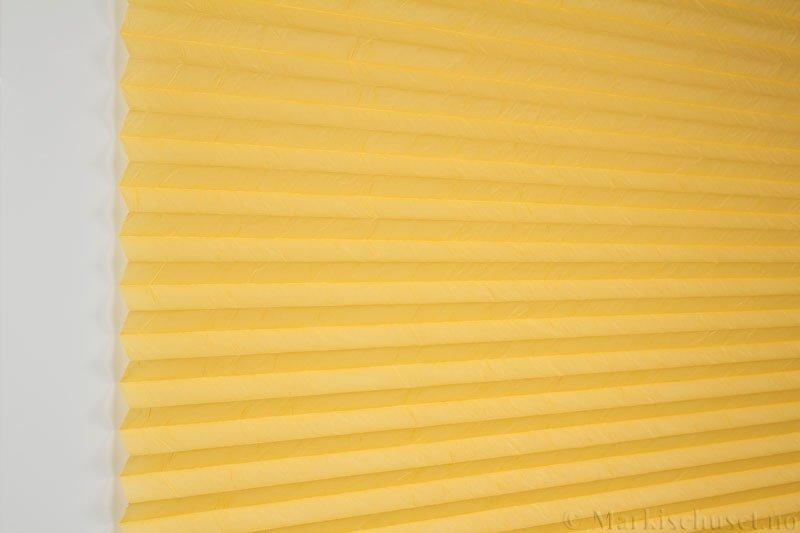 Plisségardin tekstil Crush Dustblock 290521-4199 Kinagul farge. Bildet er tatt med lys forfra.