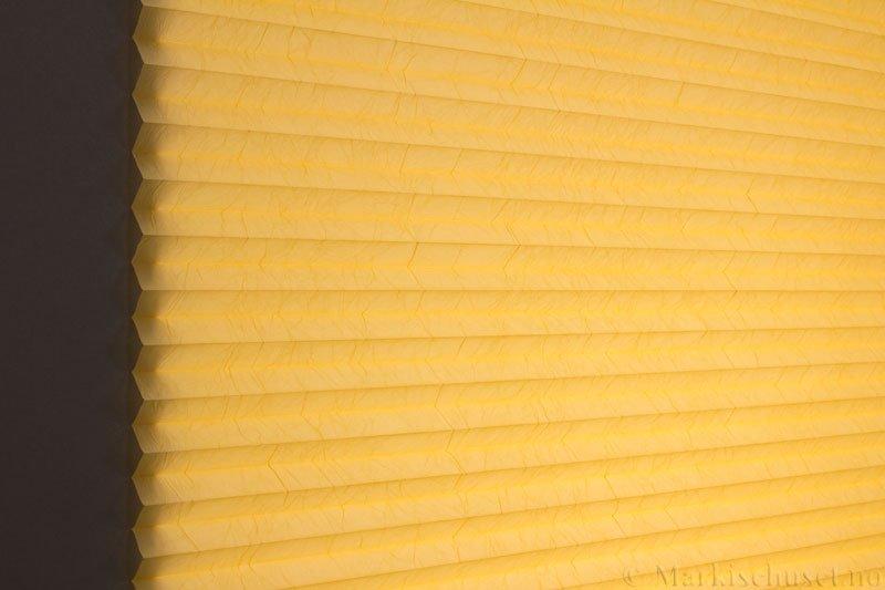 Plisségardin tekstil Crush Dustblock 290521-4199 Kinagul farge. Bildet er tatt med lys bakfra.