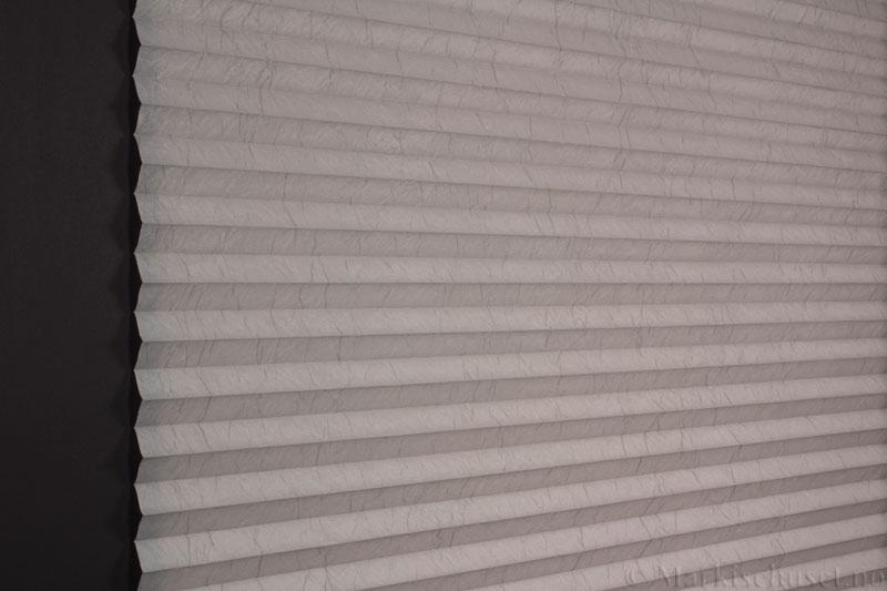 Plisségardin tekstil Crush Topar Plus 290522-1000 Elefantgrå farge. Bildet er tatt med lys bakfra.