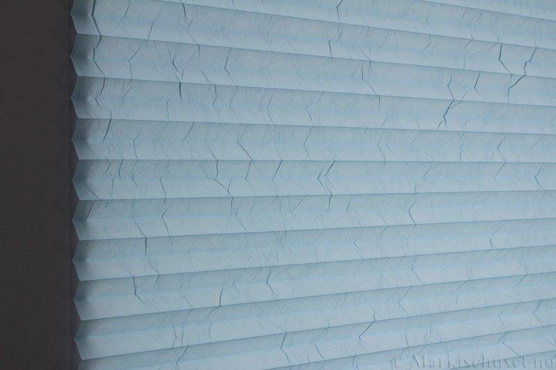 Plisségardin tekstil Crush Topar Plus 290522-2656 Salvieblå farge. Bildet er tatt med lys bakfra.