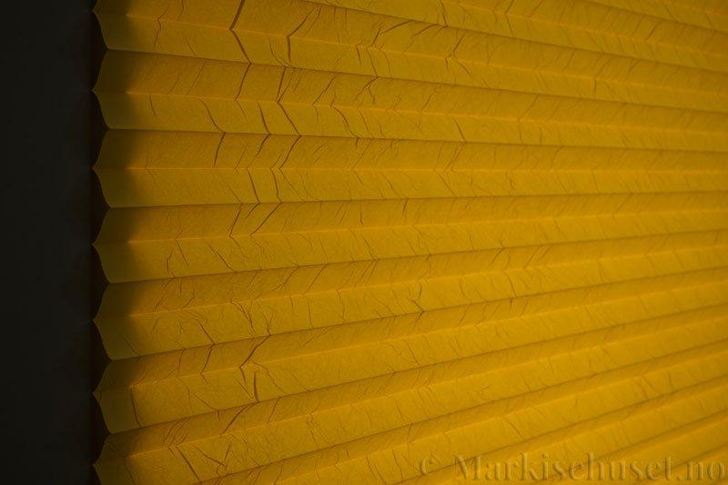 Plisségardin tekstil Crush Topar Plus 290522-4114 Gul farge. Bildet er tatt med lys bakfra.