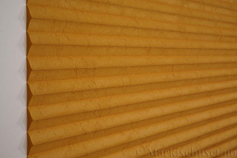 Plisségardin tekstil Crush Topar Plus 290522-4235 Honninggul farge. Bildet er tatt med lys forfra.