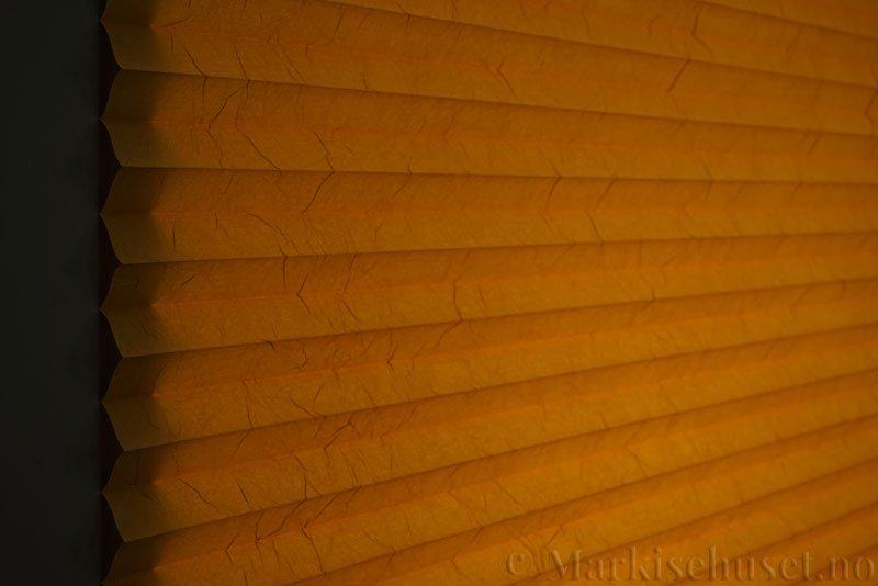 Plisségardin tekstil Crush Topar Plus 290522-4235 Honninggul farge. Bildet er tatt med lys bakfra.