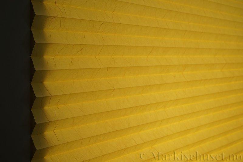 Plisségardin tekstil Crush Topar Plus 290522-4280 Maisgul farge. Bildet er tatt med lys bakfra.