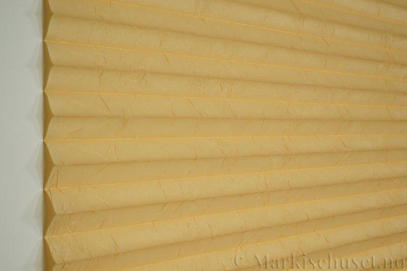 Plisségardin tekstil Crush Topar Plus 290522-4307 Strandgul farge. Bildet er tatt med lys forfra.