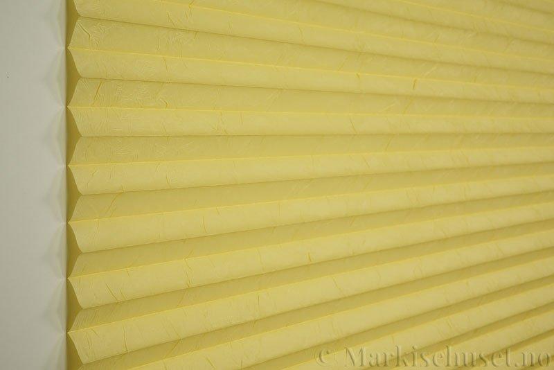 Plisségardin tekstil Crush Topar Plus 290522-4314 Pastellgul farge. Bildet er tatt med lys forfra.
