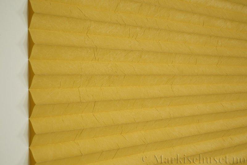 Plisségardin tekstil Crush Topar Plus 290522-4391 Okergul farge. Bildet er tatt med lys forfra.