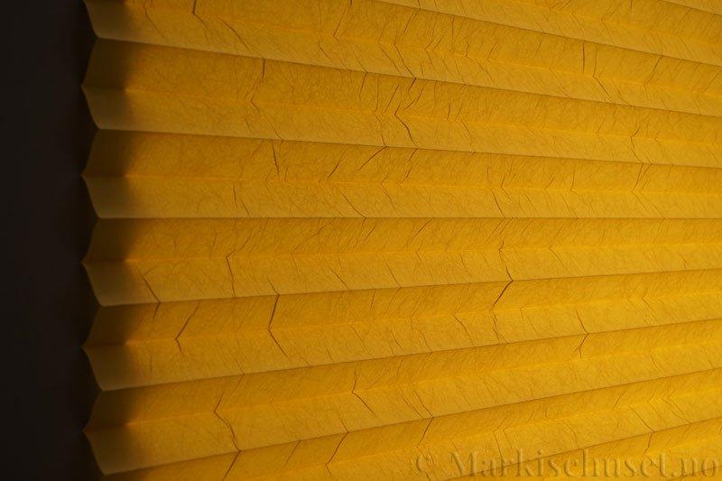 Plisségardin tekstil Crush Topar Plus 290522-4391 Okergul farge. Bildet er tatt med lys bakfra.