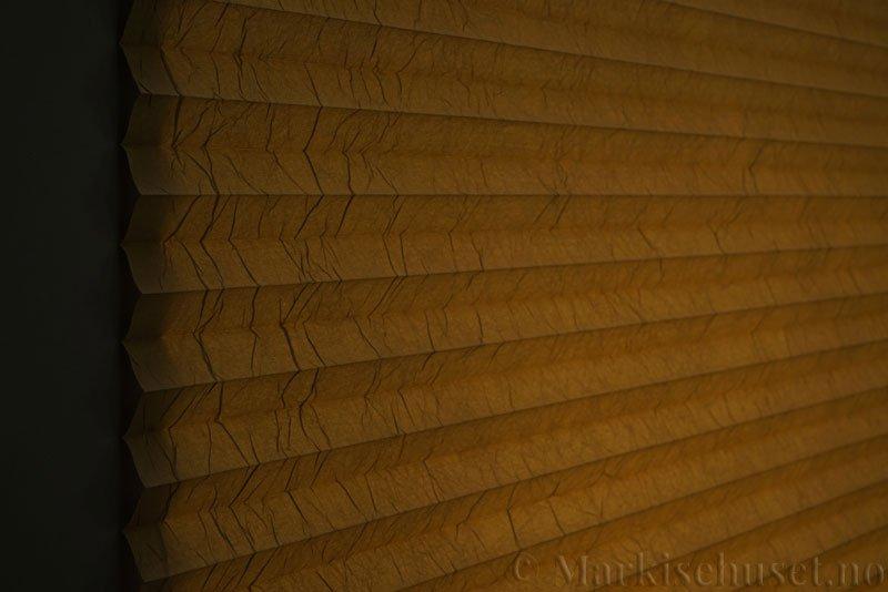 Plisségardin tekstil Crush Topar Plus 290522-4450 Olivenbrun farge. Bildet er tatt med lys bakfra.