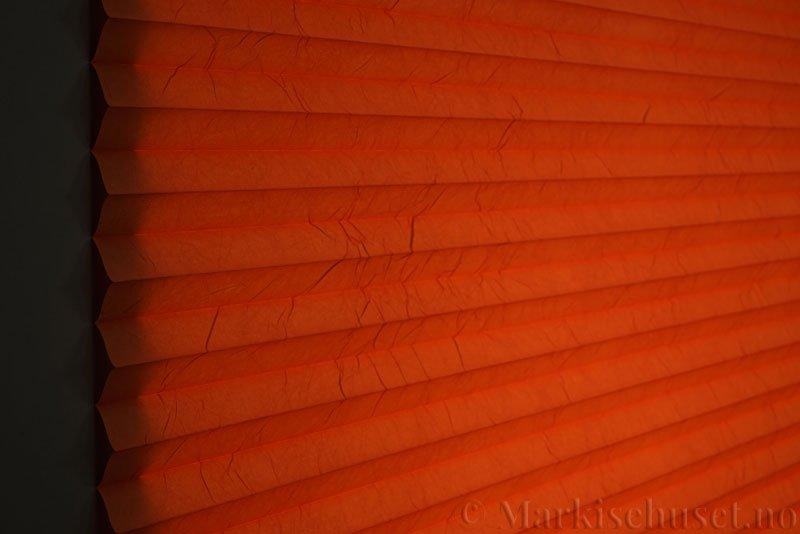 Plisségardin tekstil Crush Topar Plus 290522-5440 Varm Orange farge. Bildet er tatt med lys bakfra.