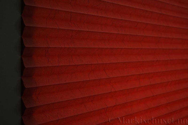 Plisségardin tekstil Crush Topar Plus 290522-5473 Rustrød farge. Bildet er tatt med lys bakfra.