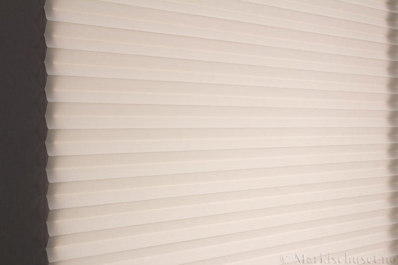 Plisségardin tekstil Chintz Topar Plus 290523-0711 Papyrus farge. Bildet er tatt med lys bakfra.