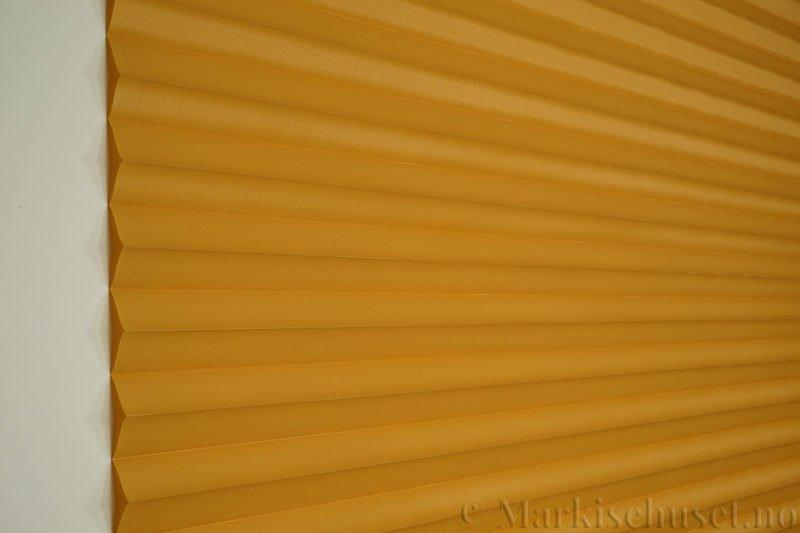 Plisségardin tekstil Chintz Topar Plus 290523-4235 Honninggul farge. Bildet er tatt med lys forfra.