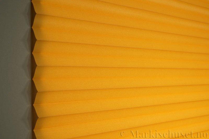 Plisségardin tekstil Chintz Topar Plus 290523-4235 Honninggul farge. Bildet er tatt med lys bakfra.