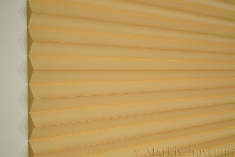 Plisségardin tekstil Chintz Topar Plus 290523-4307 Strandgul farge. Bildet er tatt med lys forfra.