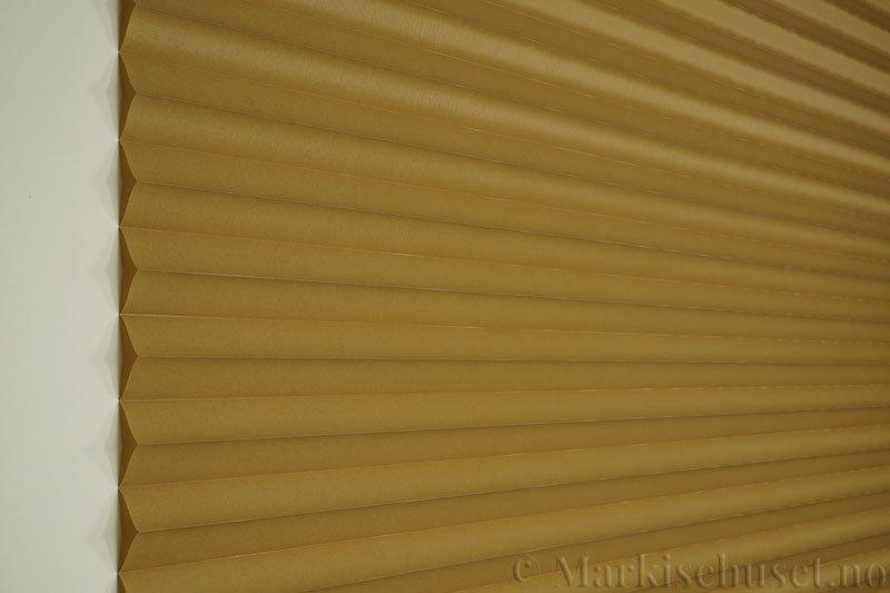 Plisségardin tekstil Chintz Topar Plus 290523-4450 Olivenbrun farge. Bildet er tatt med lys forfra.