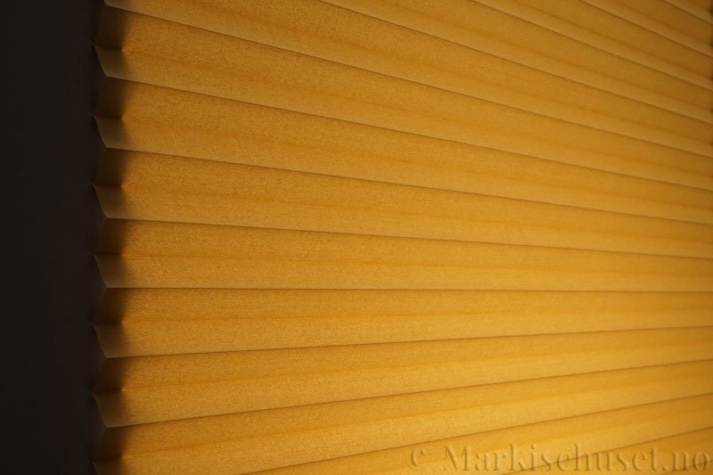 Plisségardin tekstil Chintz Topar Plus 290523-4450 Olivenbrun farge. Bildet er tatt med lys bakfra.
