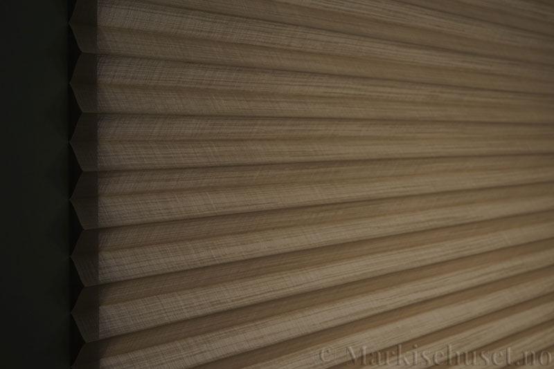 Plisségardin tekstil Cadans 290564-0999 Delfingrå farge. Bildet er tatt med lys bakfra.