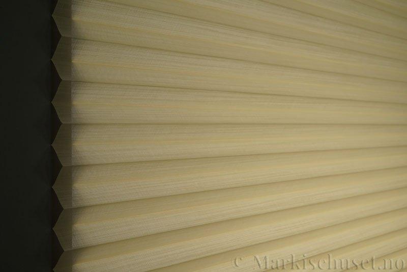 Plisségardin tekstil Cadans 290564-4680 Lys beige farge. Bildet er tatt med lys bakfra.