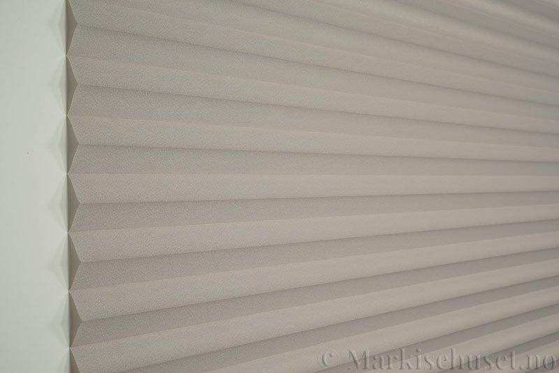 Plisségardin tekstil Crepé 290575-1230 Varmgrå farge. Bildet er tatt med lys forfra.