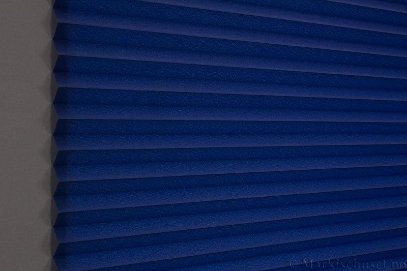 Plisségardin tekstil Crepé 290575-2650 Blå farge. Bildet er tatt med lys bakfra.