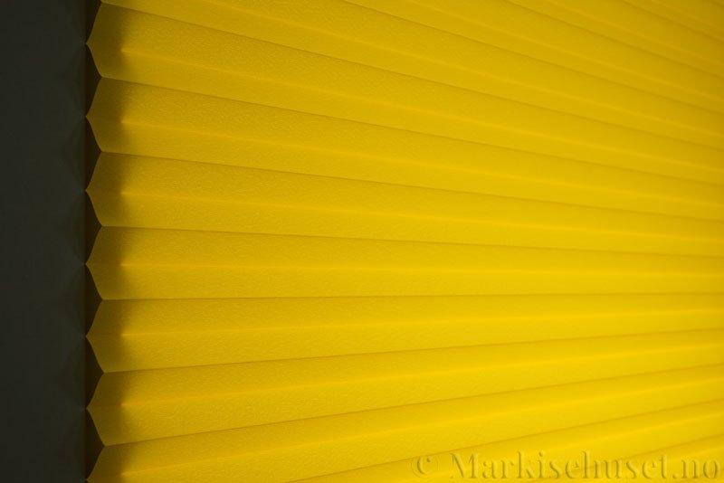 Plisségardin tekstil Crepé 290575-4141 Signalgul farge. Bildet er tatt med lys bakfra.
