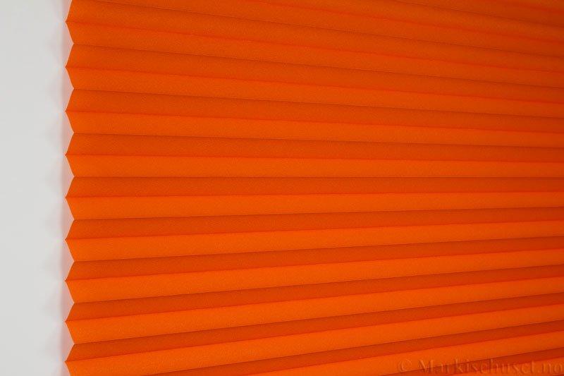 Plisségardin tekstil Crepé 290575-5495 Orange farge. Bildet er tatt med lys forfra.
