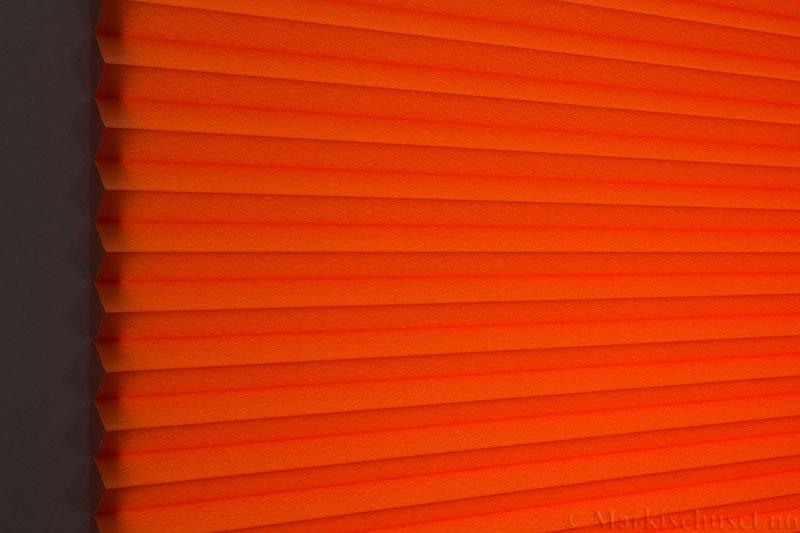 Plisségardin tekstil Crepé 290575-5495 Orange farge. Bildet er tatt med lys bakfra.