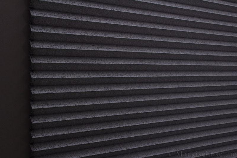 Plisségardin tekstil Manhattan Gloss 290581-1251 Sølv Antrasitt farge. Bildet er tatt med lys bakfra.